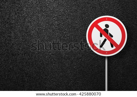 Road sign circular shape with a picture of the pedestrian. Behind the signs one can see a smooth asphalt road. The texture of the tarmac, top view. - stock photo