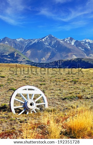 Road sign in the form of a wagon wheel. Gravel road in the desert. In the distance the snow-covered mountains. Argentine Patagonia, Perito Moreno National Park - stock photo
