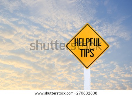 Road sign indicating Helpful Tips on blurred sky and cloud with sunlight background - stock photo