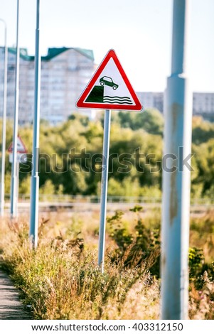 road sign of danger falling into the water - stock photo