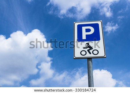 Road sign of parking motorcycle with blue sky in the background