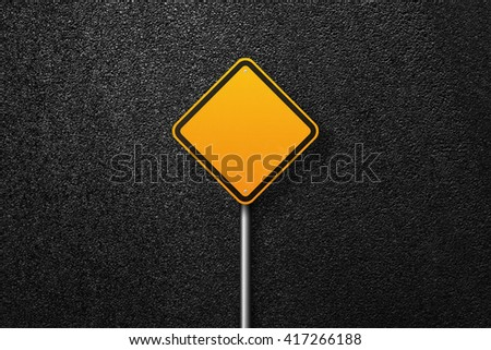 Road sign of the diamond shape. Behind the sign one can see a smooth asphalt road. The texture of the tarmac, top view. - stock photo