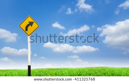road sign on green grass and blue sky