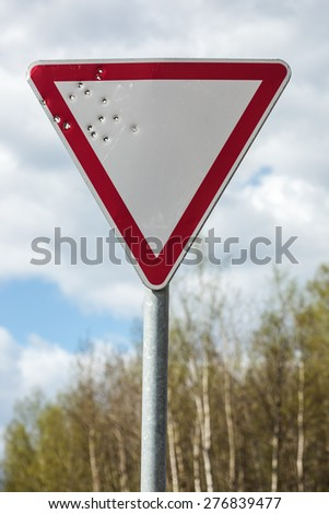 Road sign pierced with bullets.
