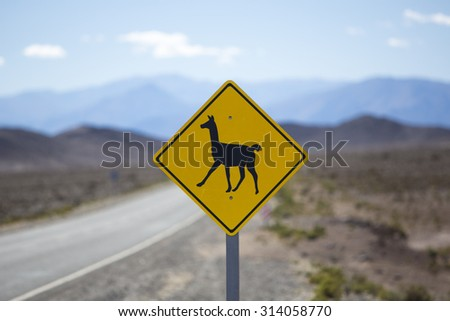 Road sign post warning on llamas crossing the famous route 40 with clear blue sky in the Northern Argentina