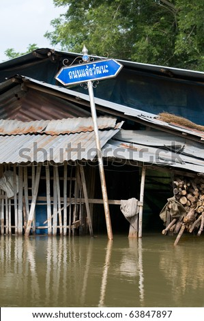 Road sign, reading Jaeng Wattana Road, in flooded village in Thailand - stock photo