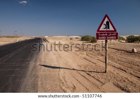 Road sign - Sand dunes, Oman - stock photo