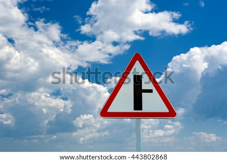 Road sign t-intersection on a background of blue sky  - stock photo