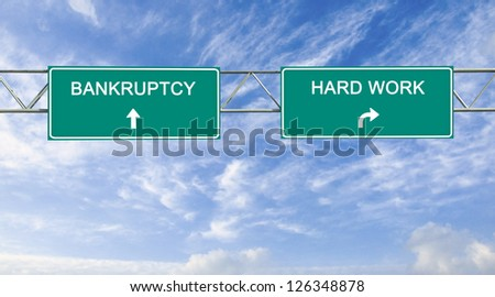 Road sign to bankruptcy and hard work - stock photo