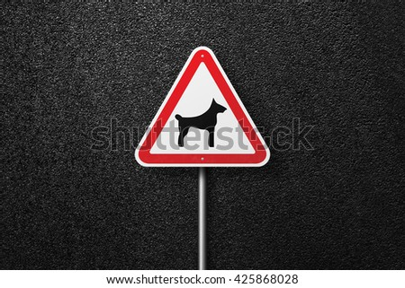 Road sign triangular shape with a picture of a dog. Behind the signs one can see a smooth asphalt road. The texture of the tarmac, top view. - stock photo