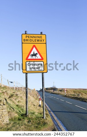 Road sign warning of  The Pennine Bridleway crossing ahead and to reduce speed on a yellow background against a clear blue sky background