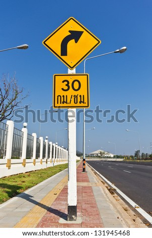 Road Sign warns Drivers to Limit Speed Ahead Dangerous Curve. - stock photo