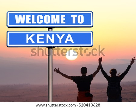 "Road sign ""Welcome to KENYA"". Young man and girl holding hands up, standing on the mountain top against sunset"