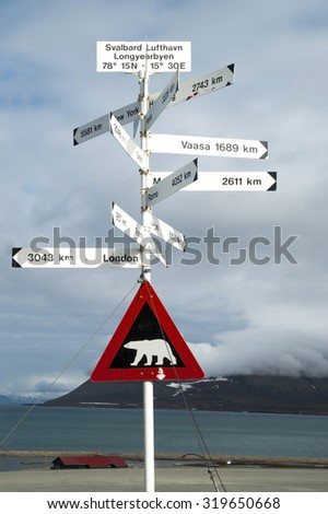 Road sign with polar bear and distances to the cities, Svalbard, Norway - stock photo