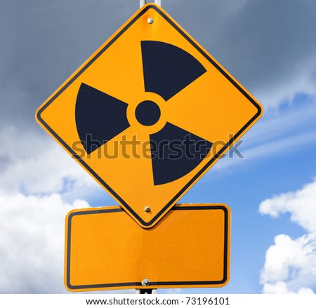Road sign with radioactivity warning symbol on it and copyspace for your message below. - stock photo
