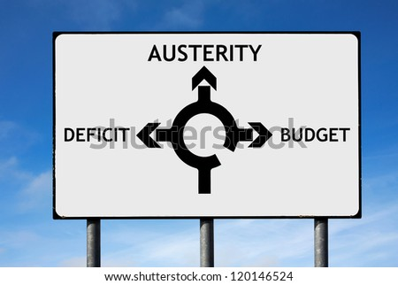 Road sign with roundabout directions pointing towards austerity deficit and budget to illustrate the financial crisis - stock photo