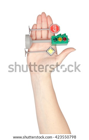 road signs and traffic light in a hand isolated on white background. driving school concept - stock photo