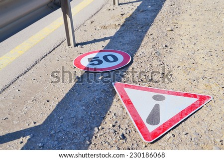 Road signs lying on the roadside - stock photo