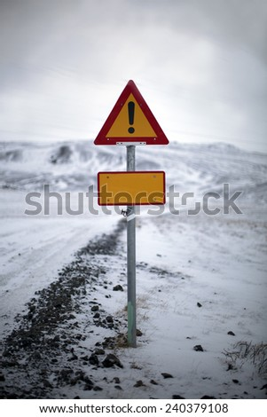 Road signs near an icy road in a winter landscape in Iceland - stock photo
