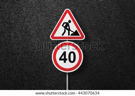 Road signs of the circular and triangular shape with a picture of a worker. Behind the signs one can see a smooth asphalt road. Road works. Speed limit. The texture of the tarmac, top view. - stock photo