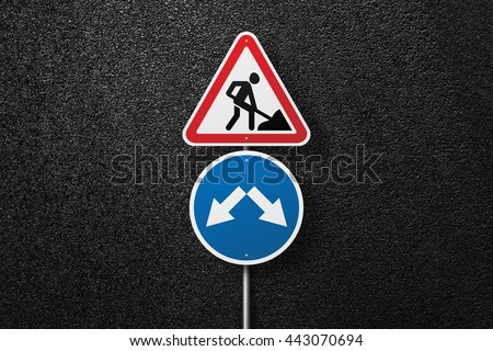 Road signs of the circular and triangular shape with a picture of a worker. Behind the signs one can see a smooth asphalt road. Road works. Pointer. Detour. The texture of the tarmac, top view. - stock photo