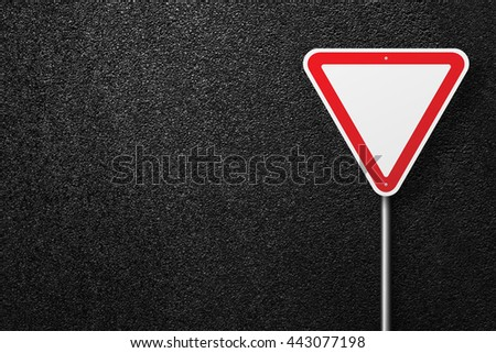 Road signs of the triangular shape. Behind the signs one can see a smooth asphalt road. Give way. The texture of the tarmac, top view. - stock photo