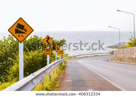Road signs on dangerous road near the sea - stock photo