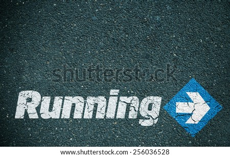 Road surface with the word running written on it with an arrow - stock photo