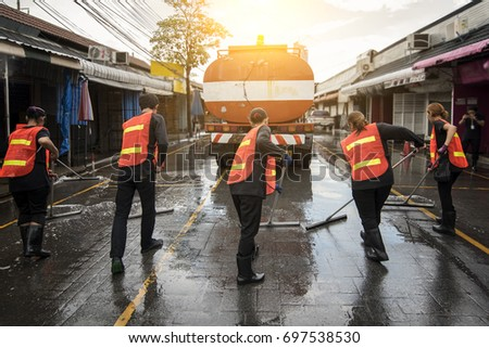 Road sweeper worker cleaning the street market with a broom.