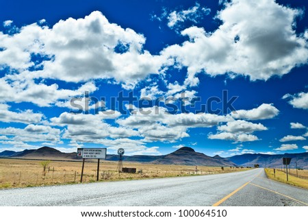 Road through a desolate landscape in South Africa - stock photo