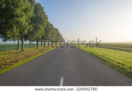 Road through a hazy countryside at sunrise - stock photo