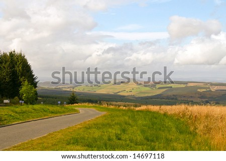 road through a mountain range landscape and rural farmland with clouds in the back