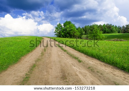 Road through a summer field over the hill with cumulus clouds on background. - stock photo