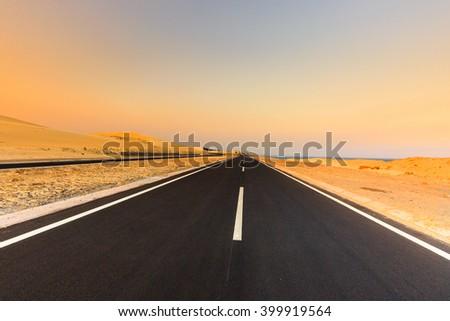 Road through desert landscape under sunset sky. Dramatic sunset sky in the desert. - stock photo