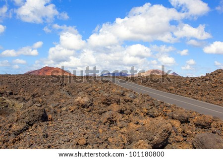 Road through lava rocks and volcanic mountains. Los Hervideros. Lanzarote - stock photo