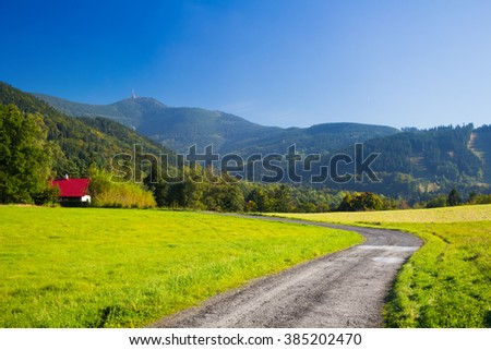 Road through meadow in mountain landscape with clear blue sky - Moravian-Silesian Beskydy - stock photo