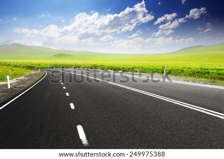 Road through meadow with cloud and sky background  - stock photo