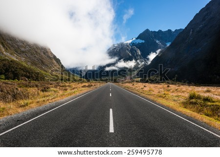 Road through mountains in New Zealand Fiordland with mist