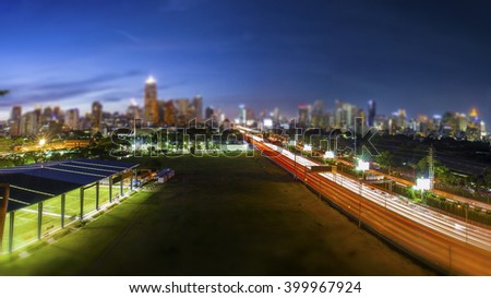 Road through the Bangkok city business area in the evening blue sky, tilt-shift effect background - stock photo