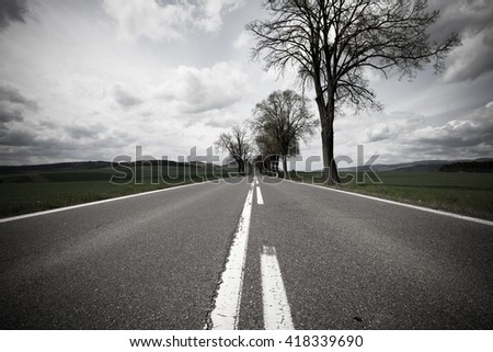 Road through the dark countryside landscape - stock photo