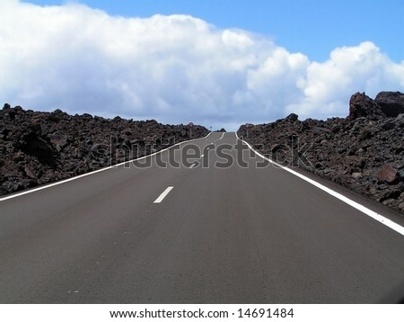 Road through the lava rocks. Lanzarote, Canary Islands. - stock photo