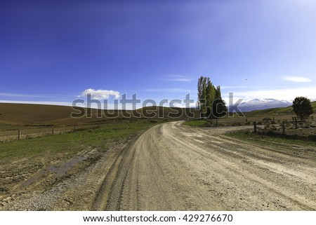 road to farmland with clouds and blue sky background - stock photo