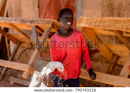 ROAD TO LAMPOUL, SENEGAL - APR 23, 2017: Unidentified Senegalese boy in red jamper holds a bag and smiles. Still many people in Senegal live in poverty