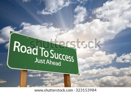 Road To Success Green Road Sign With Dramatic Clouds and Sky.
