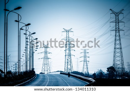 road to the High voltage towers at sunset. - stock photo