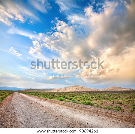 Road to the mountains through the desert at dramatic cloudy sky background