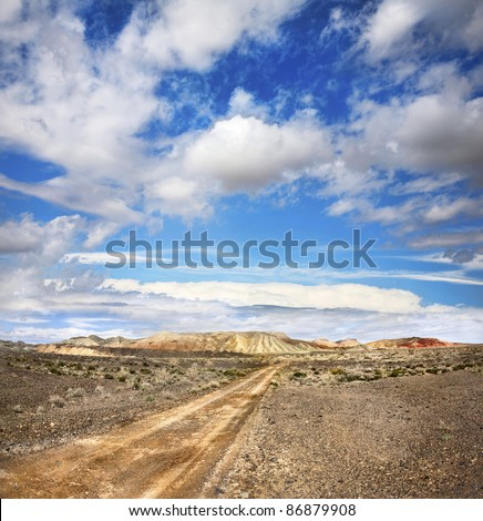 Road to the mountains through the desert at sky with clouds - stock photo