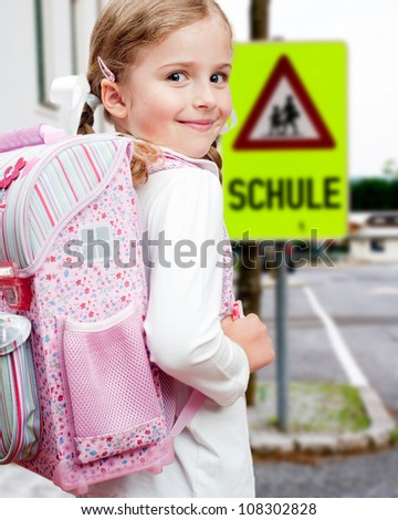 Road to the school - lovely schoolgirl on a pedestrian crossing - stock photo