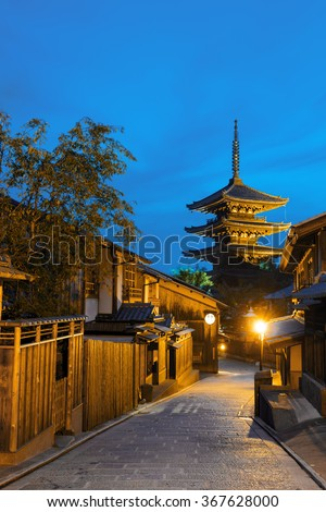 Road, traditional wooden houses and neighborhood behind Yasaka No To pagoda at blue hour in Kyoto, Japan. Vertical copy space no people present