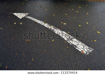 Road traffic arrow curved to left - stock photo